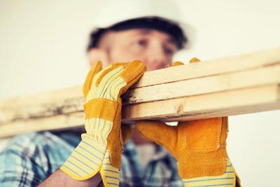 Mann trägt Dachlatten mit Leder-Arbeitshandschuhen