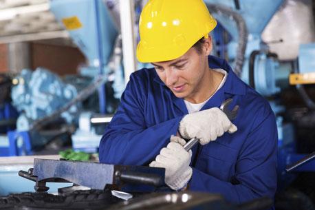 Mann mit Schraubenschlüssel trägt Arbeitshandschuhe