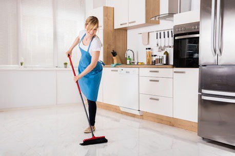 Frau fegt den Küchenboden