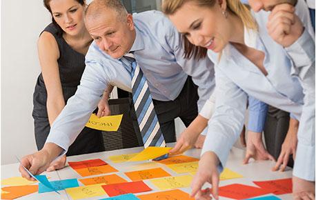 Eine Arbeitsgruppe, die auf einen Tisch voller bunter Blätter schaut