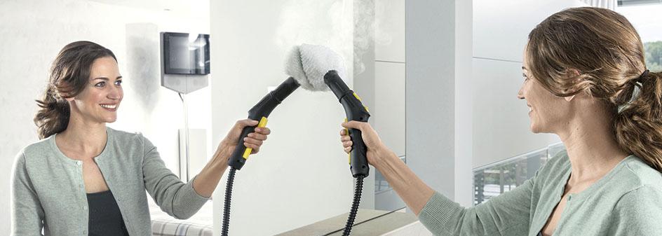 Frau reinigt mit einem Dampfreiniger ihren Spiegel im Badezimmer