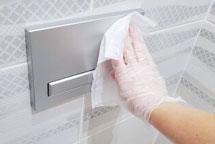 Desinfizieren einer Toiletten-Drückerplatte mit einem Desinfektionstuch für Oberflächen