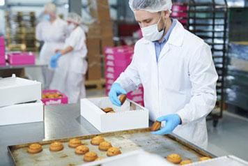 Mann verpackt Gebäck mit blauen Einmalhandschuhe in der Lebensmittelindustrie