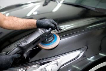 Mann polliert mit schwarzen Einmalhandschuhen ein Auto in der Werkstatt