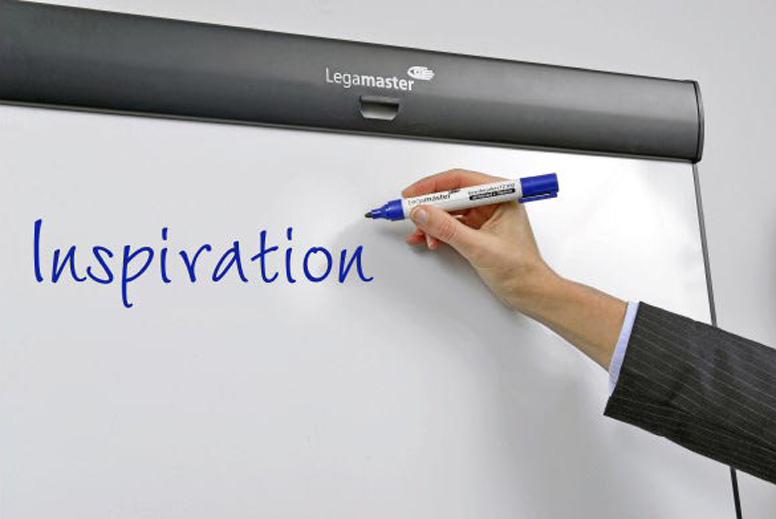 Eine Hand, die mit einem Stift das Wort inspiration an ein Flipchart schreibt