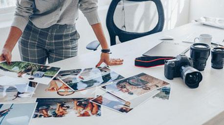 Profifotografin beurteilt Fotoausdrucke auf dem Schreibtisch