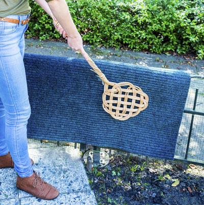 Teppich, der gerade mit einem Teppichklopfer von Staub gereinigt wird