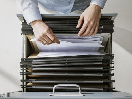 Frau sortiert Unterlagen in ein Hängeregister