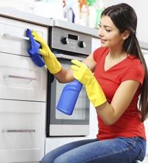 Frau säubert die Griffe der Küchenmöbel
