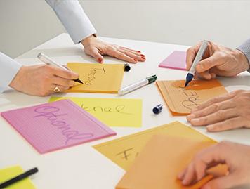 Ein Team beschriftet Karteikarten für eine Präsenation