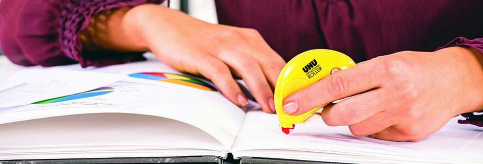 Junge Frau klebt mit einem Kleberoller etwas in ihr Notizbuch