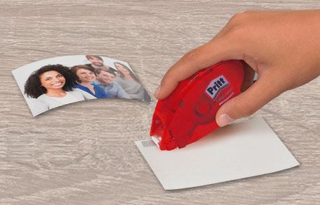 Bilder werden mithilfe eines Kleberollers aufgeklebt