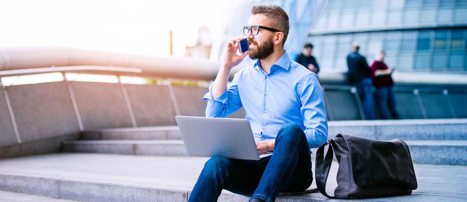 Business Mann sitzt auf einer Treppe mit seinem Laptop und telefoniert
