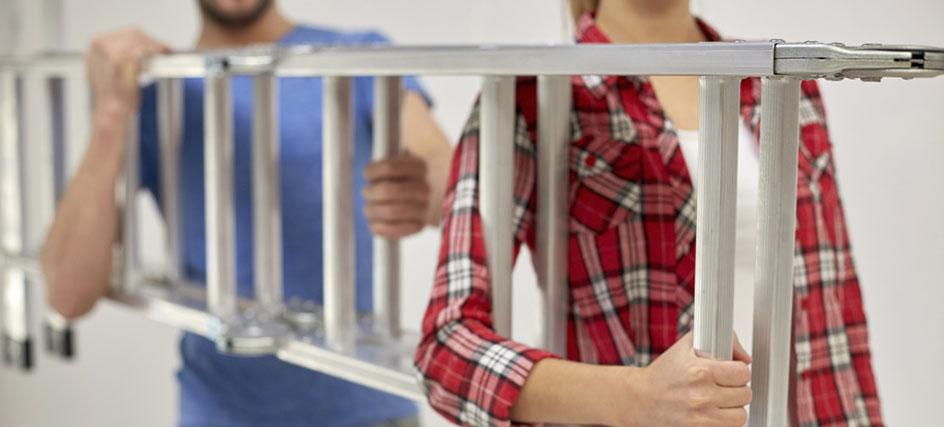 Junges Paar mit einer Aluminium-Leiter