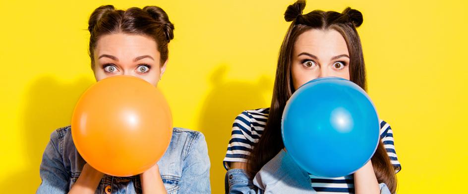 Junge Frauen blaßen Luftballons auf
