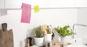 Klebende Notizzettel als Einkaufszettel an einem Küchenschrank