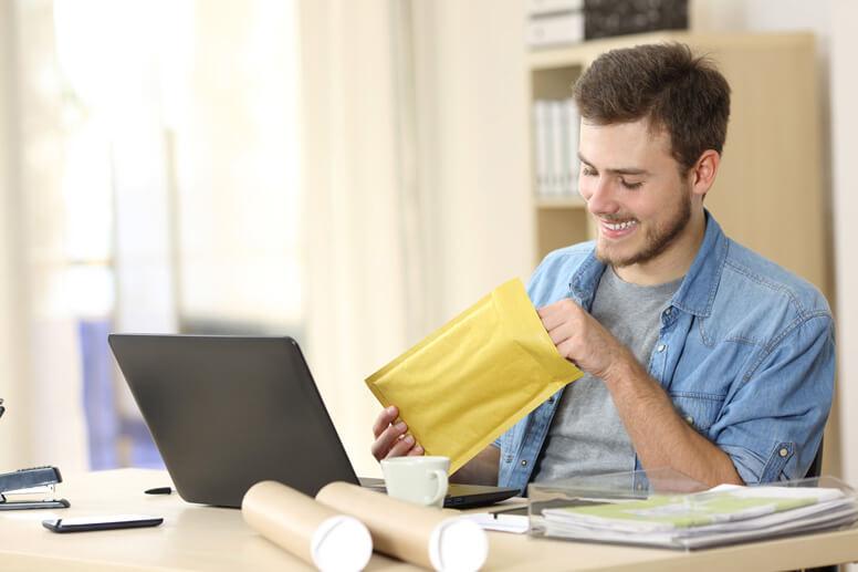 Büromitarbeiter öffnet Versandtasche am Arbeitsplatz