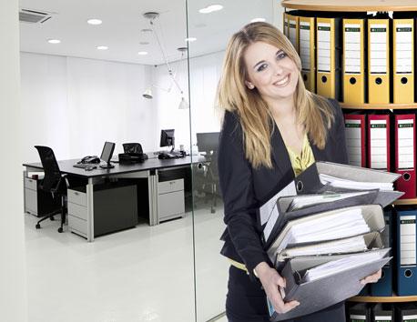 Junge Büroanagestellte steht lächelnd mit einem Stapel Ordner vor einer Ordnerdrehsäule