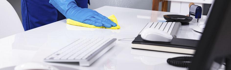 Schreibtisch wird mit einem gelben Putztuch gesäubert