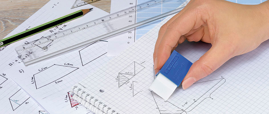Person radiert auf einem karrierten Block mit geometrischen Formeln