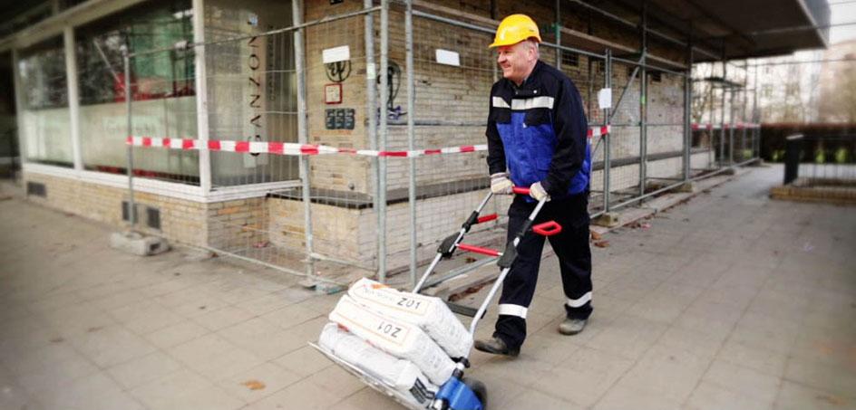 Bauarbeiter transportiert drei Säcke Zementmörtel mit einer Ruxxac Sackkarre