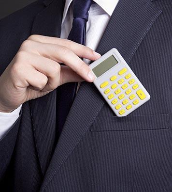 Mann steckt einen Taschenrechner in die Sakkotasche