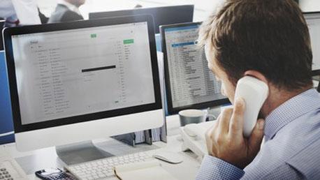 Ein Mann telefoniert mit einem kabelgebundenen Telefon am Arbeitsplatz