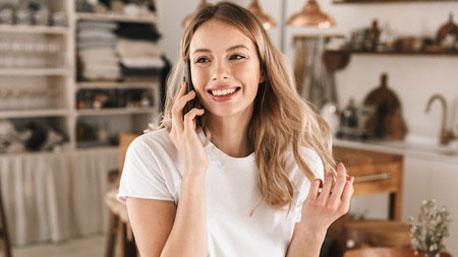 Eine Frau telefoniert Zuhause mit einem Mobilteil